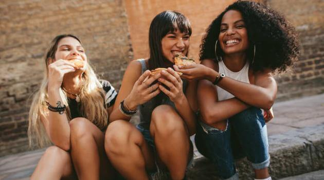 Shutterstock: three young women friends sitting on sidewalk and sharing pizza slices