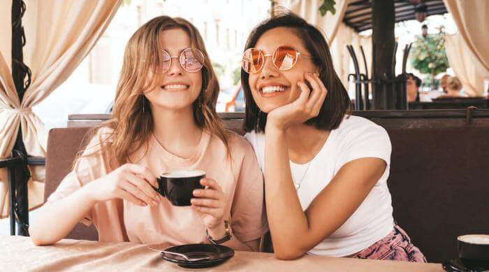 Shutterstock: two young women smiling in a hipster outdoor cafe, wearing summer casual clothes and vintage round sunglasses, one is drinking a latte
