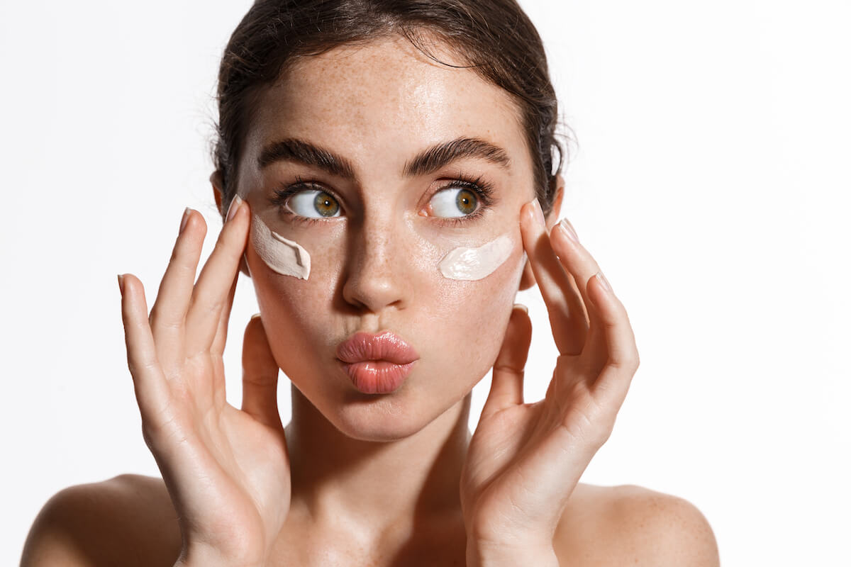 Shutterstock: Close up beauty girl with freckles and thick eyebrows, applying moisturizing skincare cream, lotion or mask for skin lifting and anti-aging detoxifying effect, white background.