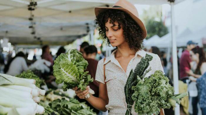 Shutterstock: woman buying fresh kale at a busy farmers' market