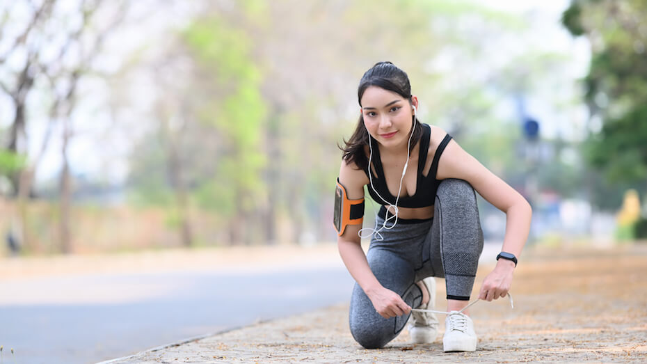 Shutterstock: Smiling fitness woman tie shoelaces getting ready for jogging outdoors.