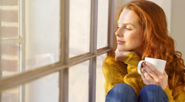 Shutterstock: woman sitting on window sill in soft lighting, holding a coffee mug and looking out the window