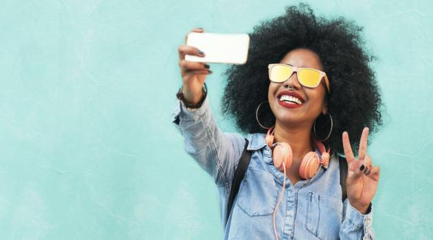 shutterstock-woman-taking-selfie-smiling-and-doing-peace-sign-050221-e1619984411407-articleH-050221