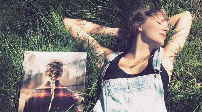 Instagram @taylorswift in grass with evermore vinyl