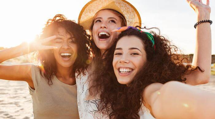 Shutterstock: Three cheerful girls friends in summer clothes taking a selfie at the beach