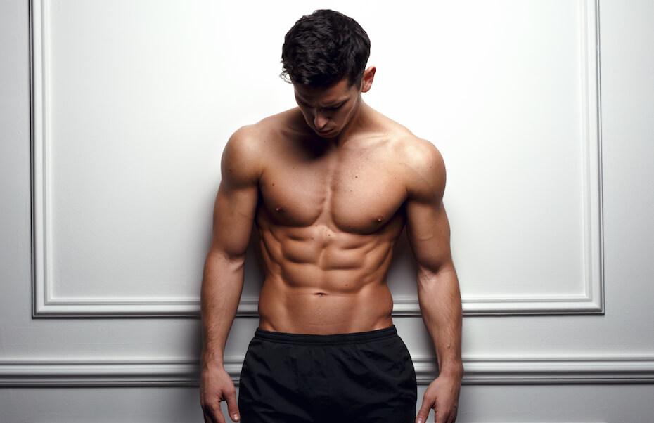 Shutterstock: Stylish shirtless man at the white wall looking down, Horizontal studio shot.