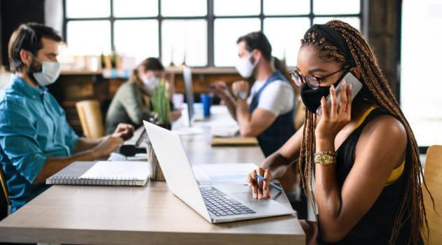 Shutterstock: young businesspeople with face masks working indoors in office