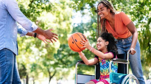 Shutterstock: two adults and one girl who is in a wheelchair playing basketball in park