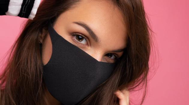 Shutterstock: close up photo of woman wearing face mask against a pink background