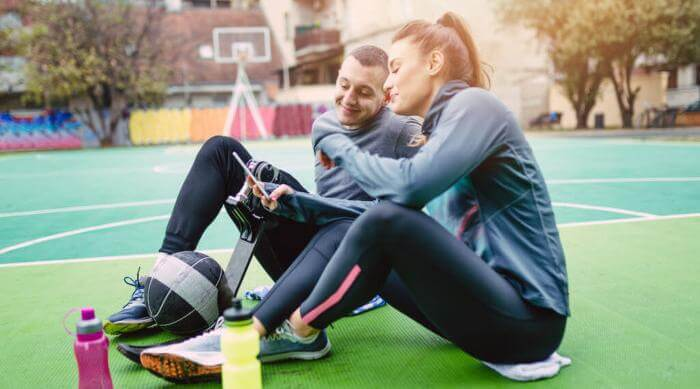 Shutterstock: two friends, on with prosthetic leg, sitting together in basketball court, looking at an iPhone