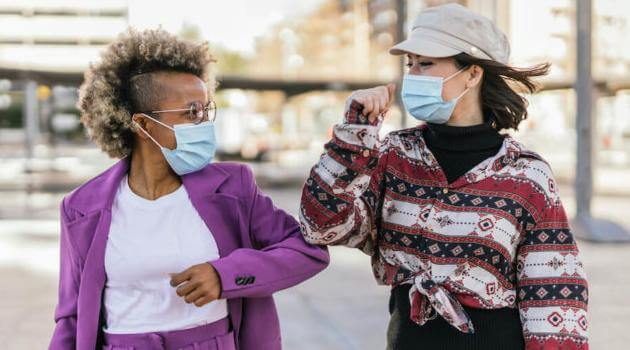 Shutterstock: two woman friends walking down a city street, talking and wearing protective masks