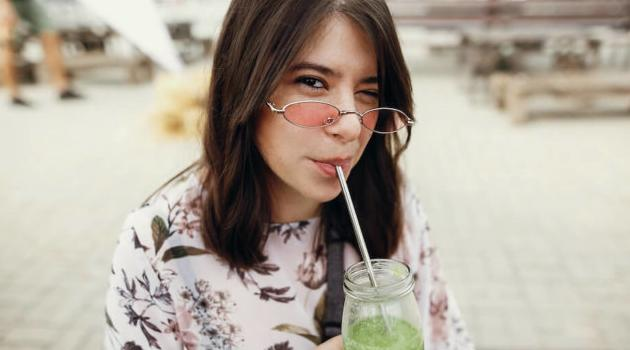 Shutterstock: woman drinking spinach smoothie in a glass jar with metal reusable straw