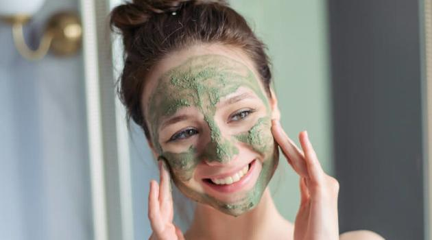 Shutterstock: woman smiling in mirror, putting on a green (slightly grey) clay-like skincare face mask