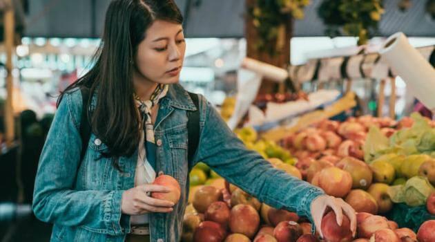 Shutterstock: woman picking apples in farmers market
