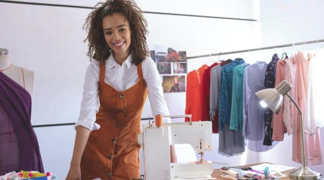 fashion designer standing at table in design studio