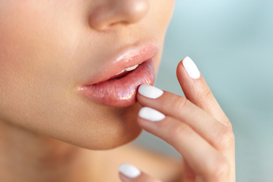 Shutterstock: Lip Protection. Closeup of Beautiful Young Woman Healthy Lips. Female Model Mouth With Smooth Perfect Skin And Natural Manicure Touching Her Plush Lips. Lip Care And Beauty. High Resolution