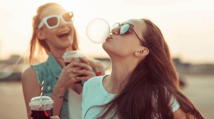 Shutterstock: Girls having fun blowing bubble near sunset