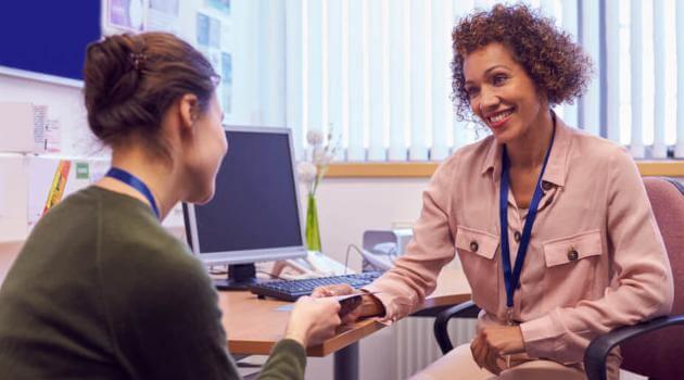 Shutterstock: academic advisor talking to student