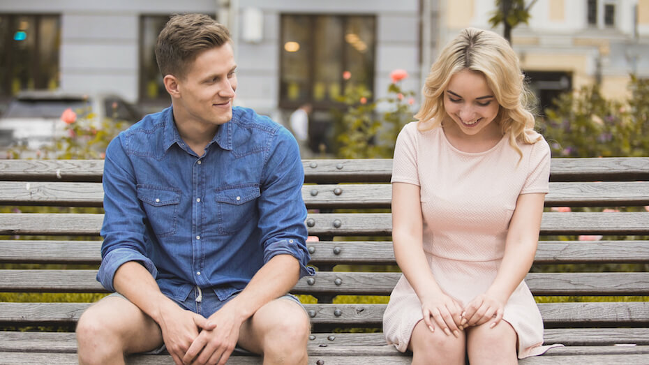 Shutterstock: Shy blonde girl smiling, attractive guy flirting with beautiful woman on bench