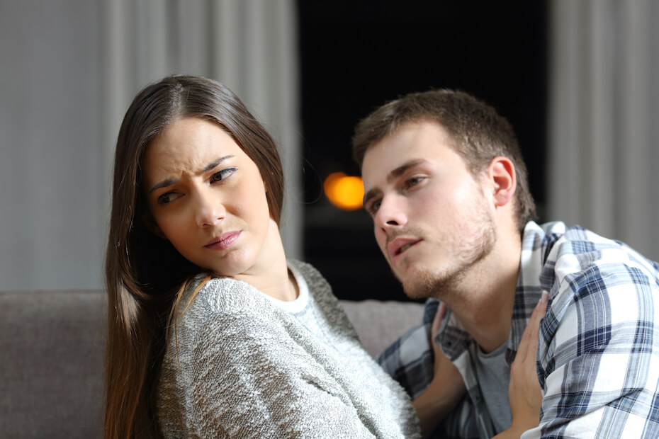 Shutterstock: Insistent man trying to get kiss and his worried girlfriend denying on a couch in the night at home