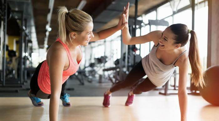 Shutterstock: Beautiful women working out in gym together