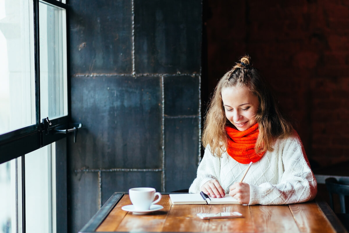Shutterstock: Woman left hand writing journal on small notebook in cafe with big window.