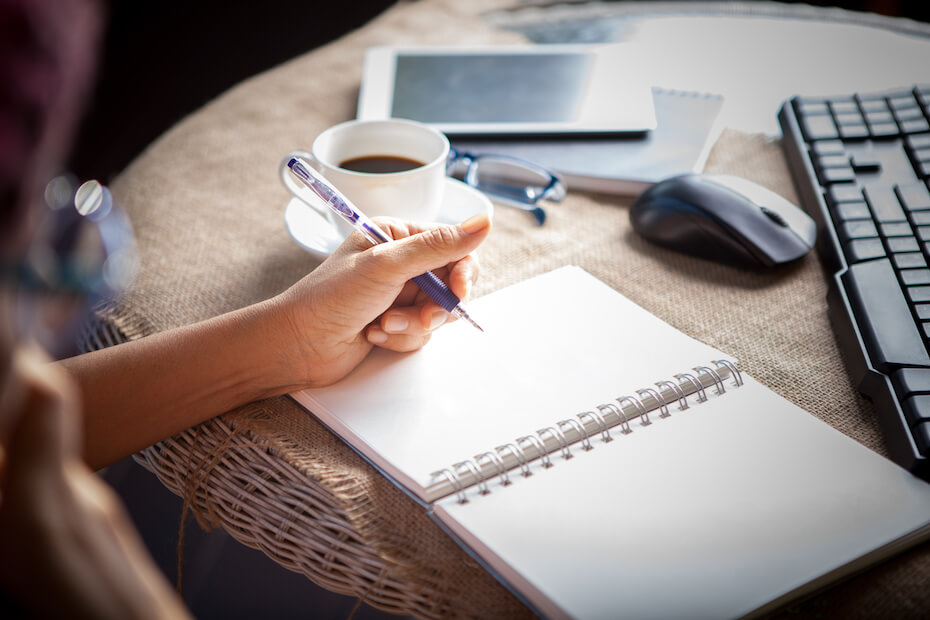 Shutterstock: woman left hand writing on paper book ,on table shot