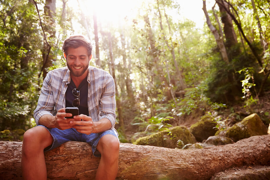 Shutterstock: Man looking at phone text in forest smiling