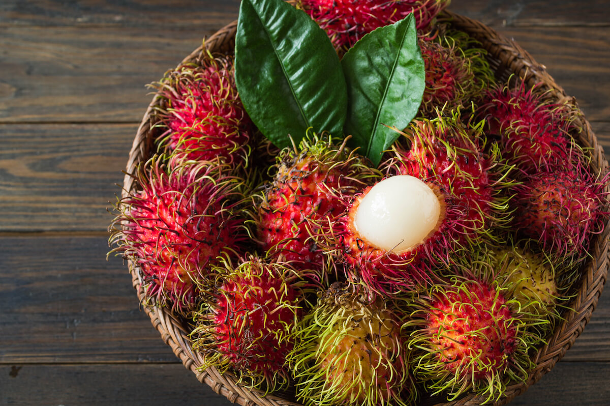 Shutterstock: Rambutan, Thai fruits in a bamboo basket placed on an old wooden table