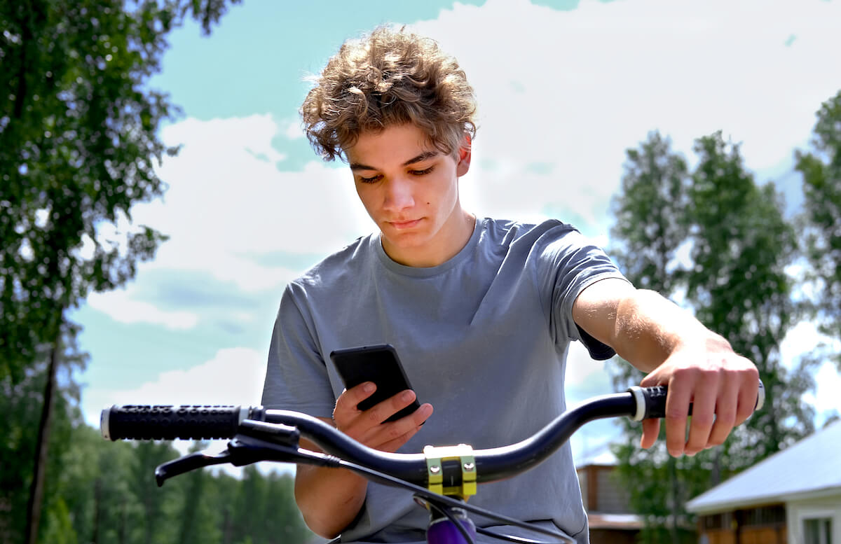 Shutterstock: Teen boy looking at phone while riding bike