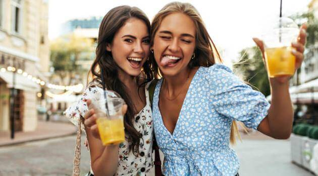 Two female friends posing holding juice