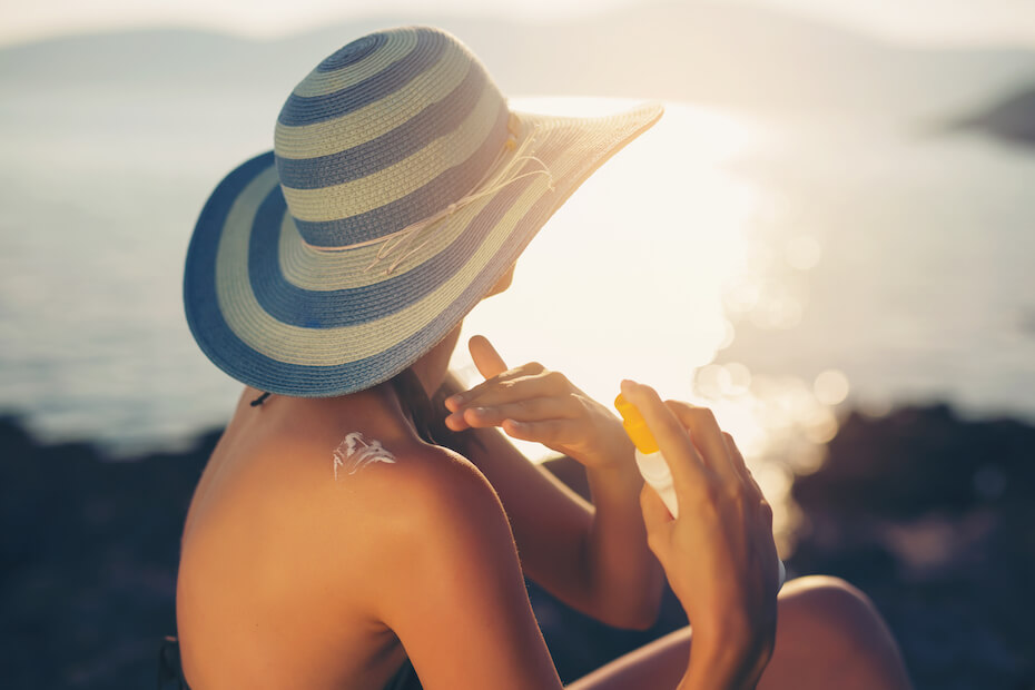 Shutterstock: Young woman in sunglasses holding bottle of sunscreen lotion, spraying sunblock cream on shoulder before tanning