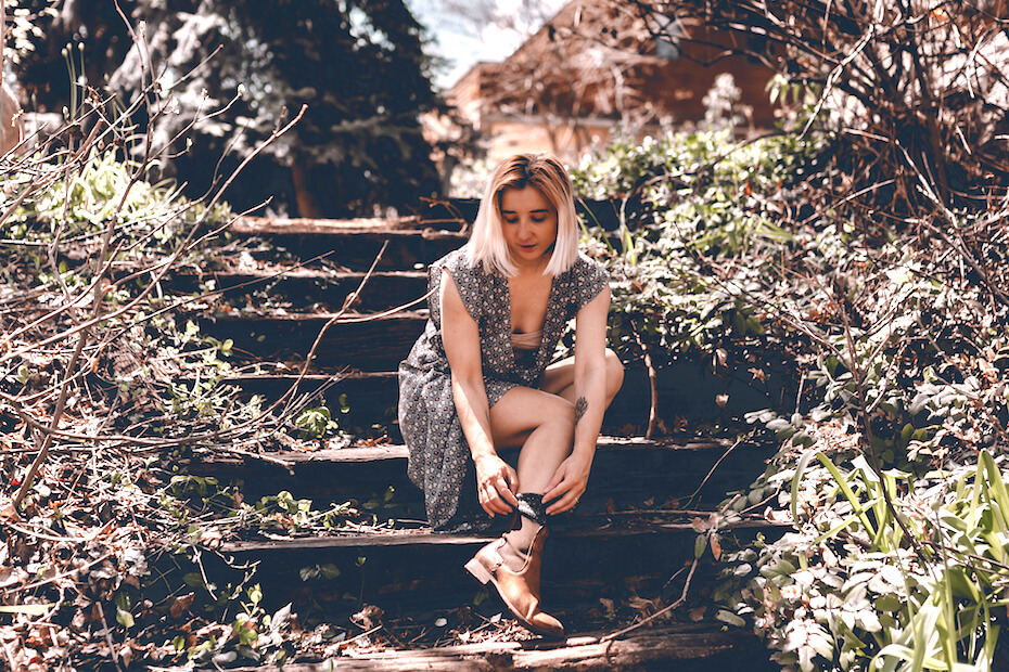 Shutterstock: Young hipster woman travels in Colorado forest. Long dress, chelsea boots, black hat. Blonde millennial lady. Freedom. Escape home. Local traveling. Exploring places. Travel locally. Travel anxiety.