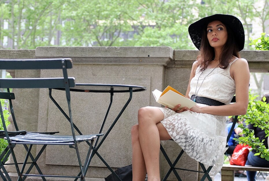 Shutterstock: Rich beautiful brunette looking up from reading a book wearing a white dress with white belt sitting in a urban city park during a summer day