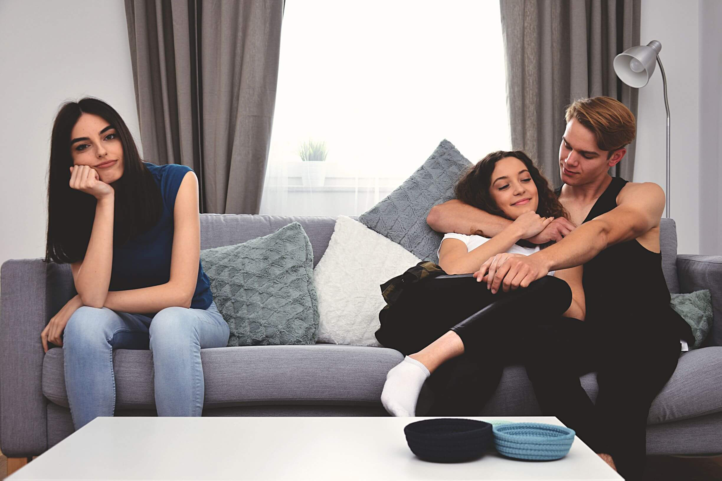 A teenage couple cuddles on a couch while their friend sits at the other end alone and looks unhappy