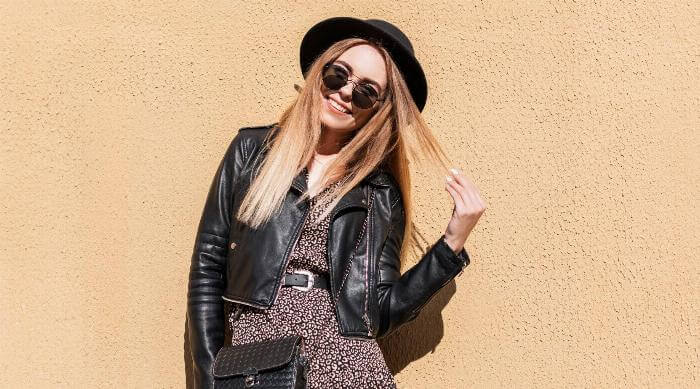 A young blonde girl wearing a leather jacket and accessories stands against a wall and twirls her hair