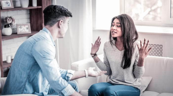 Shutterstock: Expressively gesturing. Swearing couple having quarrel about their life together and woman raising her hands in strong gesture