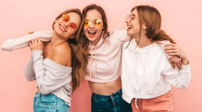 Three friends wearing sunglasses smile while standing against a pink wall