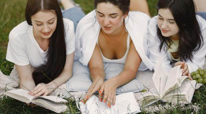 Shutterstock: Group of girls reads books in a park