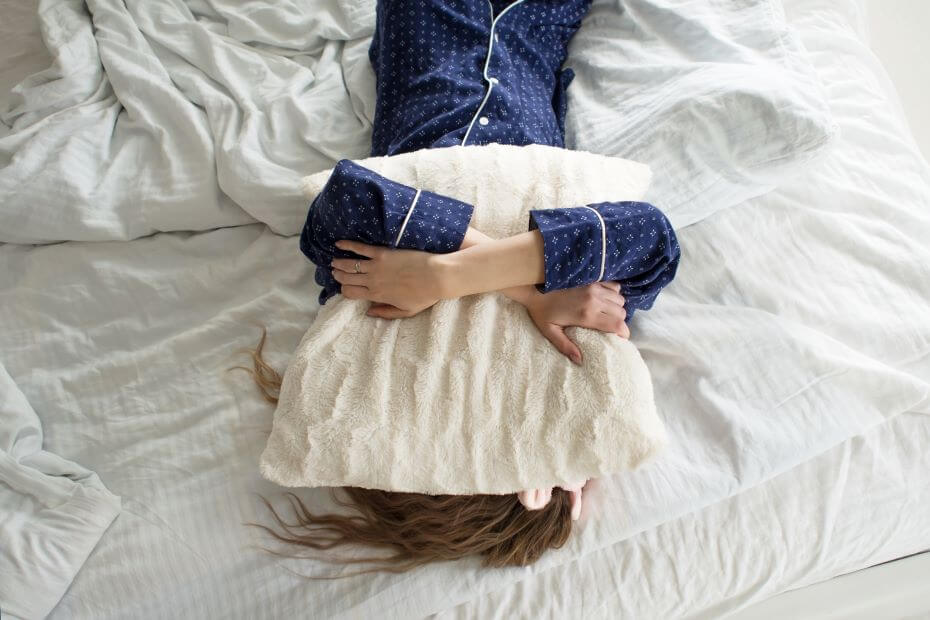A young girl holds a pillow over her face in the morning while still in bed