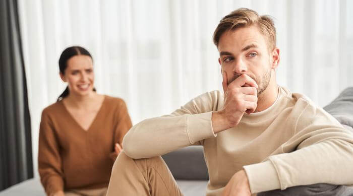 Shutterstock: Tell me the truth. Depressed brunette angry woman sitting on the sofa and gesticulating while talking to her husband. Annoyed man ignored his wife and pondering while looking away