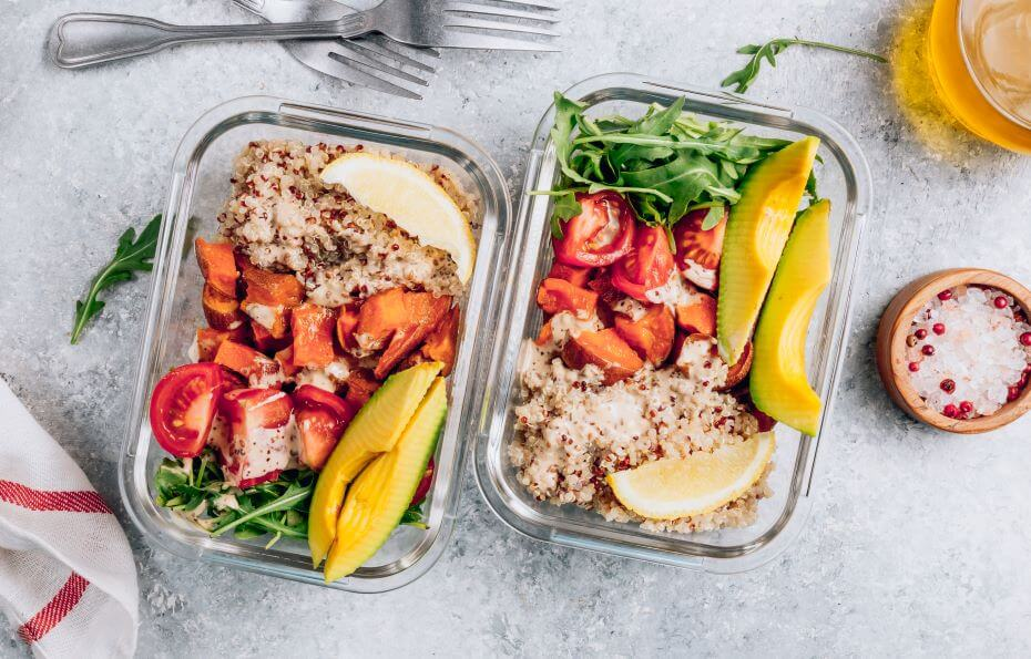 Two boxes of meal prepped healthy food sit on a counter