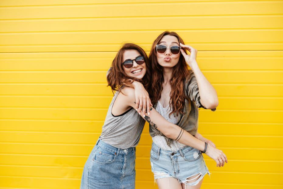 Two teen girls smile against a yellow brick wall