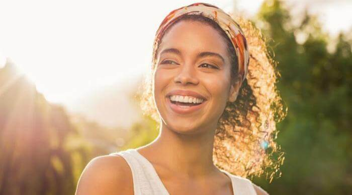 A young girl smiles with the sun shining behind her