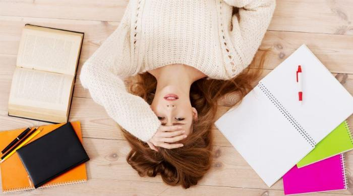 A young girl lays on the floor surrounded by notebooks looking stressed