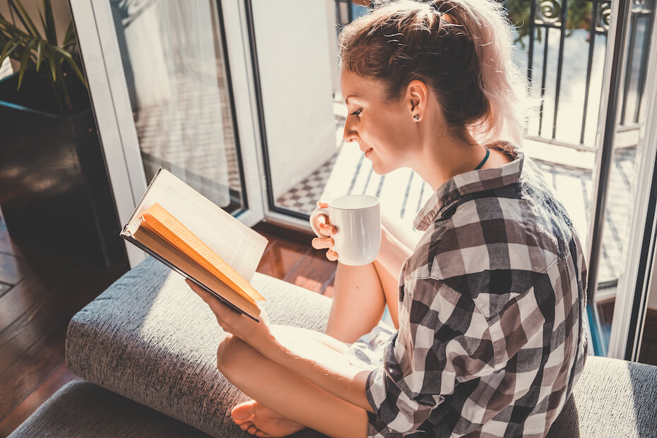 Young pretty woman sitting at opened window drinking coffee and reading a book enjoys of rest
