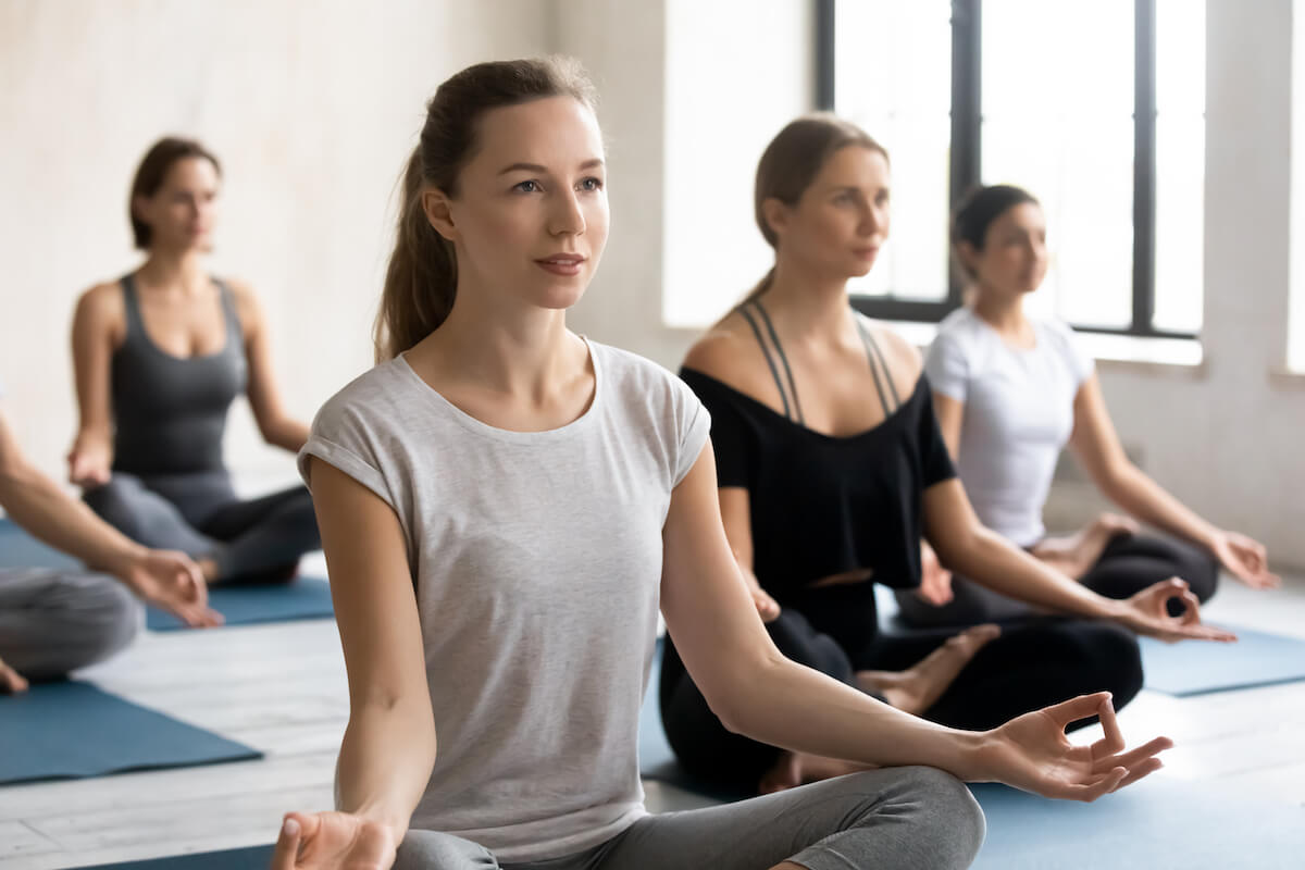 Shutterstock: Female yoga instructor and young like-minded group of people wearing comfy sportswear sitting in lotus position do meditation practice calming mind relaxing after work out during yoga session concept