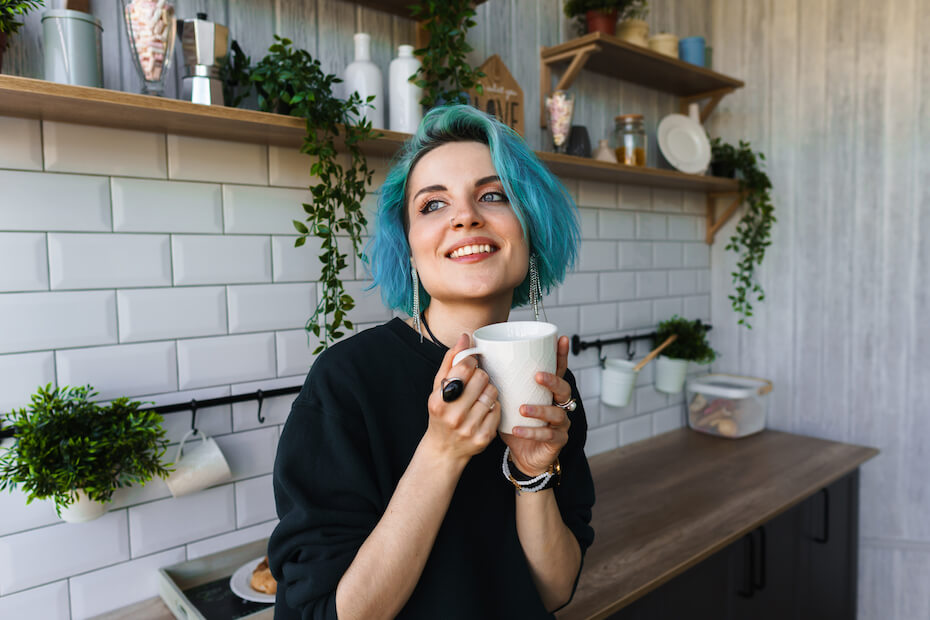 Shutterstock: Beautiful girl drinks tee leaning on a table in a bright kitchen with a modern design