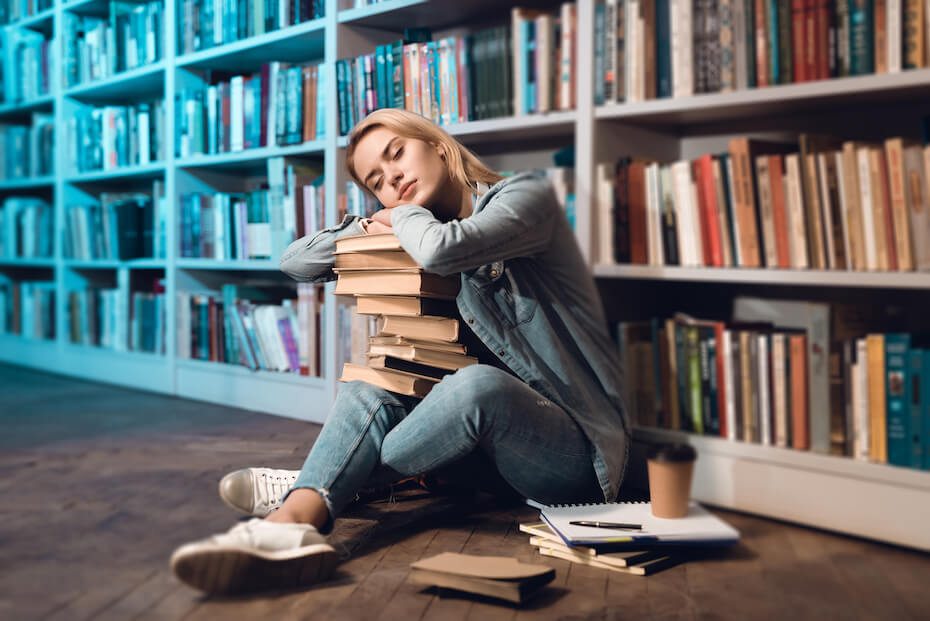 Shutterstock: Beautiful girl sitting on the floor near a large shelf with books. Young girl fell asleep on a book while sitting near a shelf with books in the library.