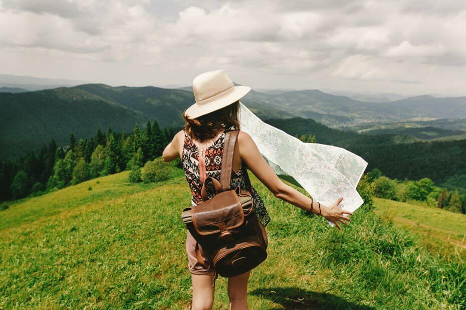 A young girl holds a map on a hilltop while traveling